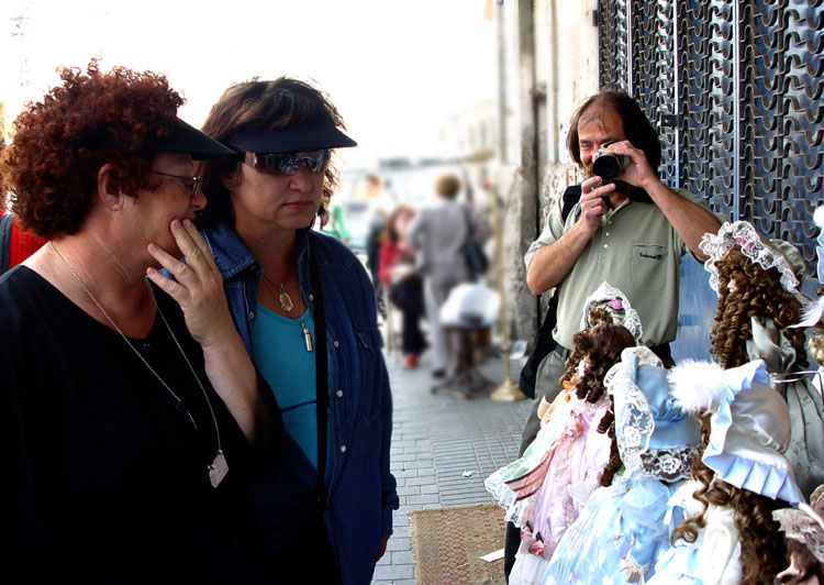 Miri and zipi look at dolls standing on a table top outside a shop, while eddie photographs me