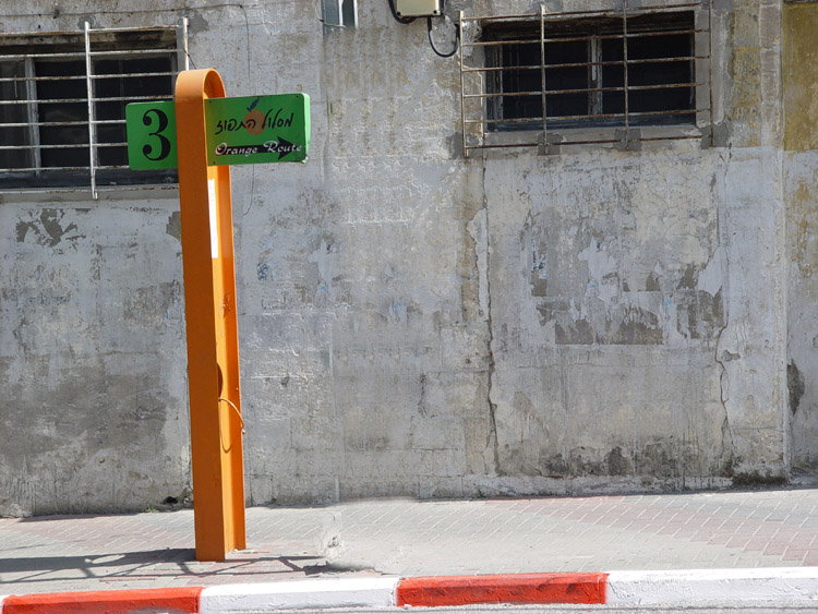 """a sign post painted orange with the number 3 , an arrow pointing right and the words """"orange route"""" written on it"""""""
